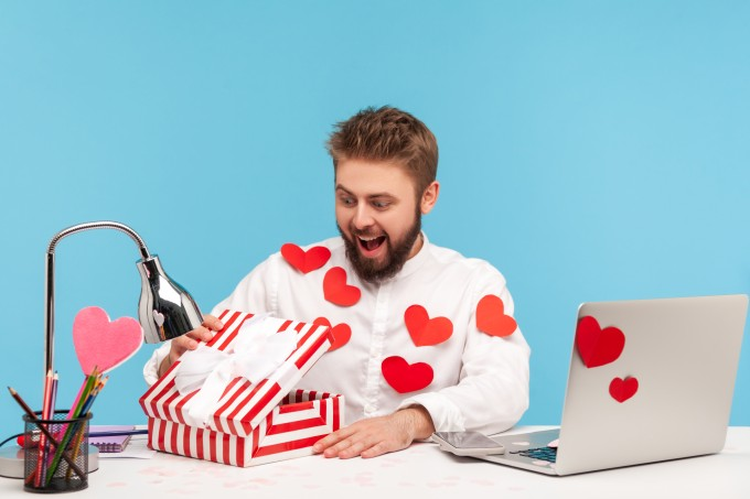 Happy surprised man with beard in white shirt in red sticky hearts unboxing present and looking inside with smile, satisfied with gift
