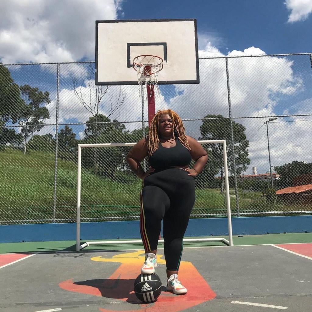Ellen, atleta de peso, posando para foto em uma quadra de basquete com a bola apoiada no chão