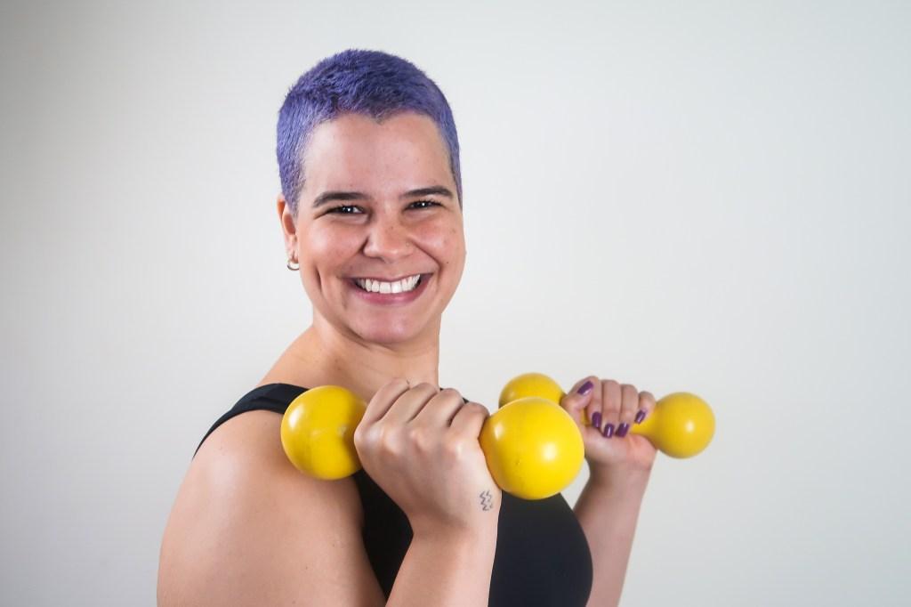Natália Mota, do Saúde GG, em um fundo branco e pesinhos de mão amarelos