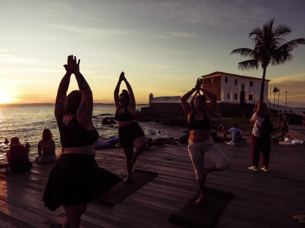 Mulheres gordas fazendo yoga ao ar livre, no pôr-do-sol