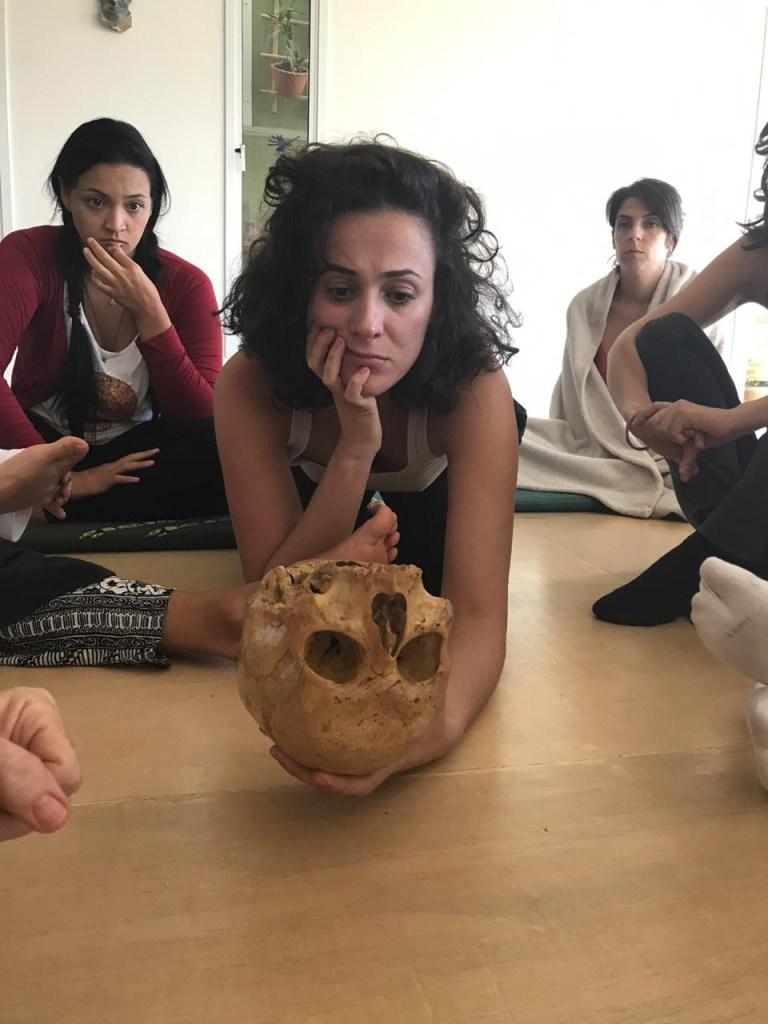Aluna em um grupo de eutonia analisa uma réplica de crânio da face |