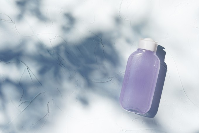 Bottle of micelar water or tonic, product for skincare beautyon textured concrete background with shadows.