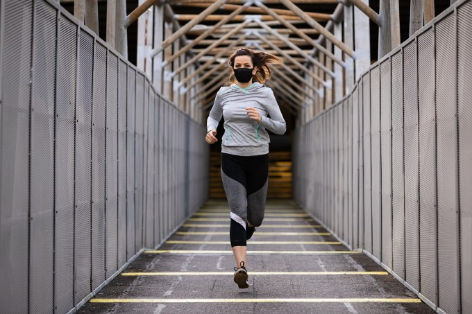 Woman doing running exercise wearing face mask and grey jumper