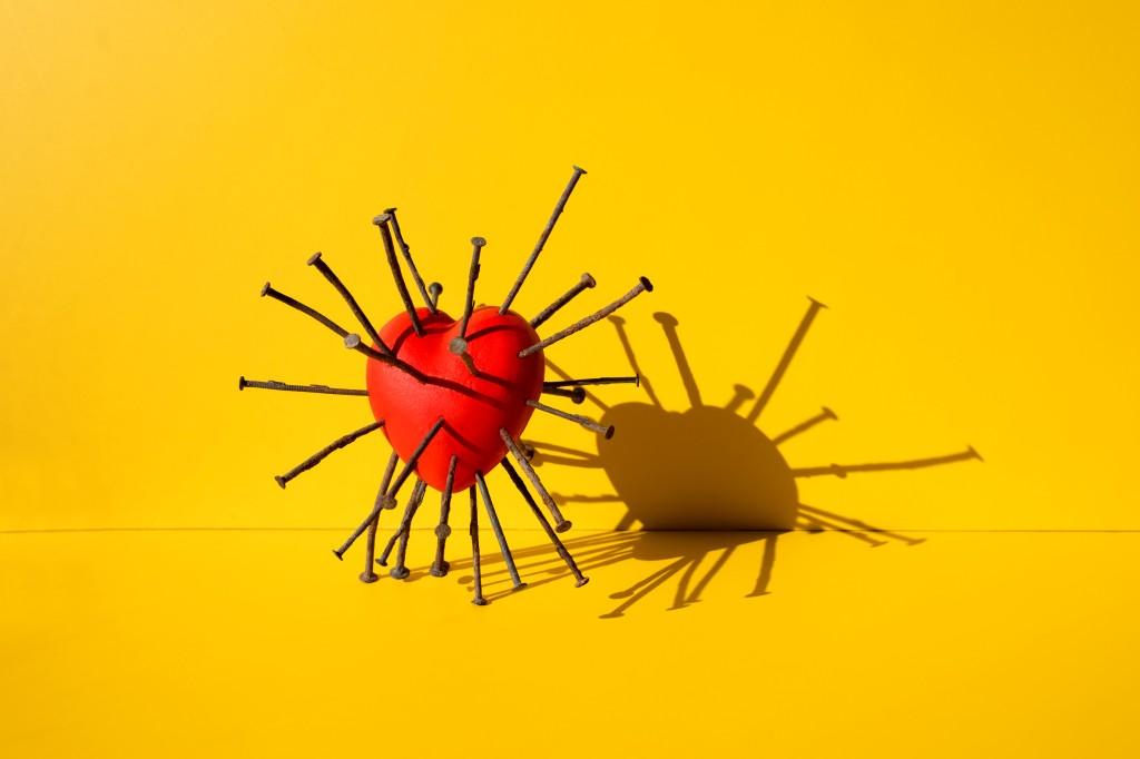 Ilustração de um coração com diversos pregos perfurados na superfície