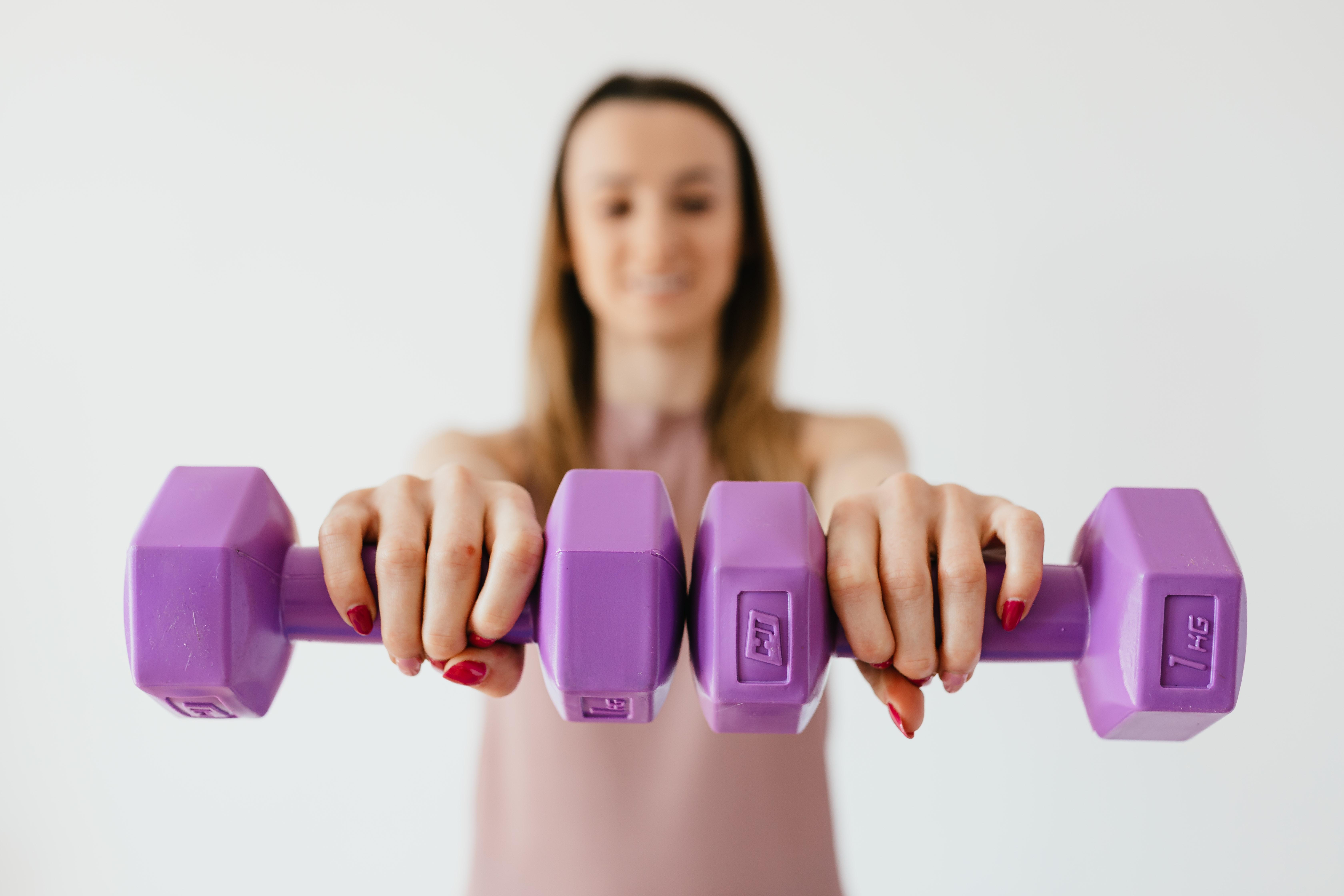 Mulher segurando dois pesos de academia roxos nas mãos