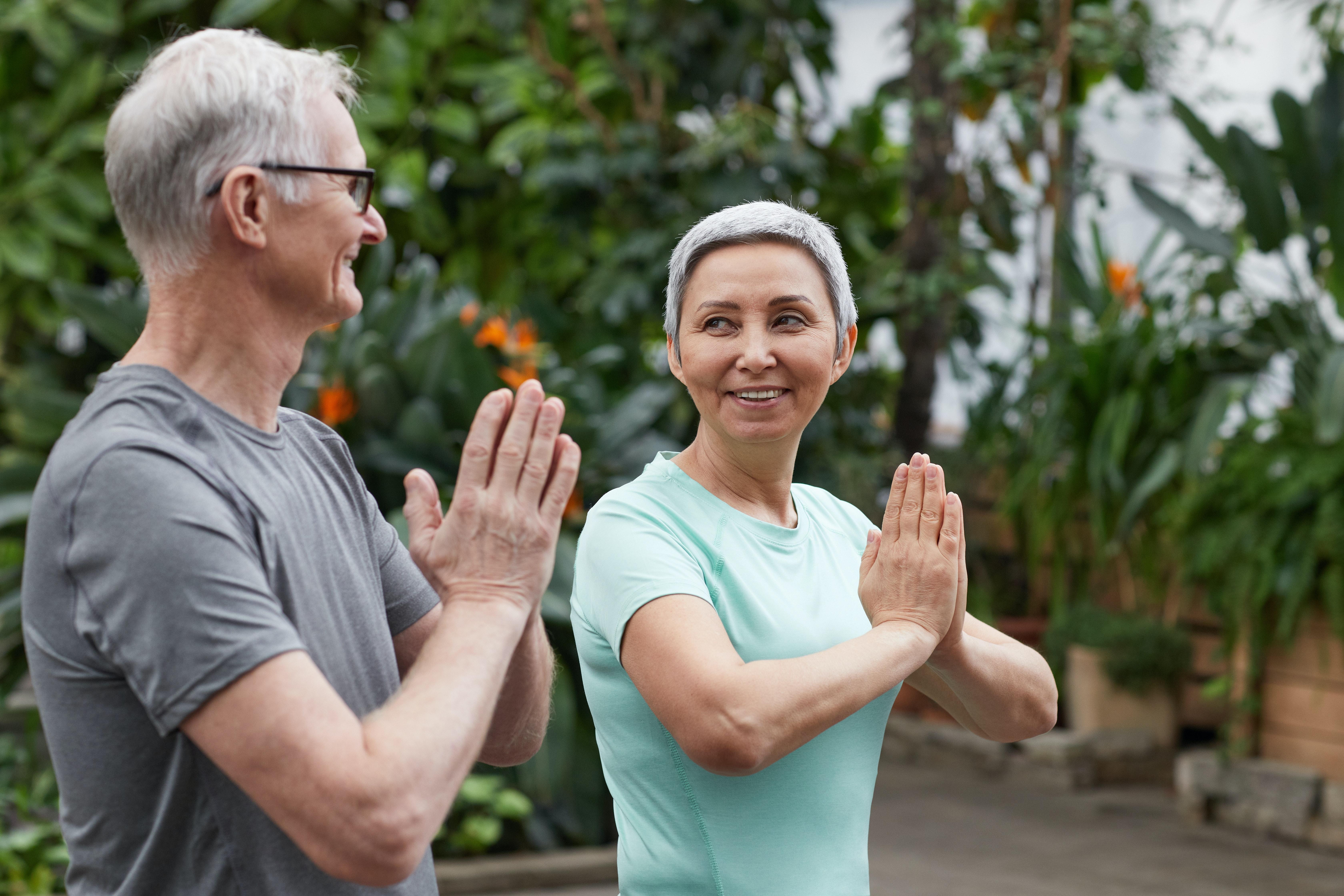 Senhor e senhora fazendo yoga juntos, se olhando e sorrindo.