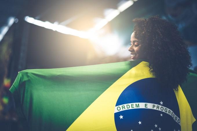 Jovem estendendo a bandeira do Brasil
