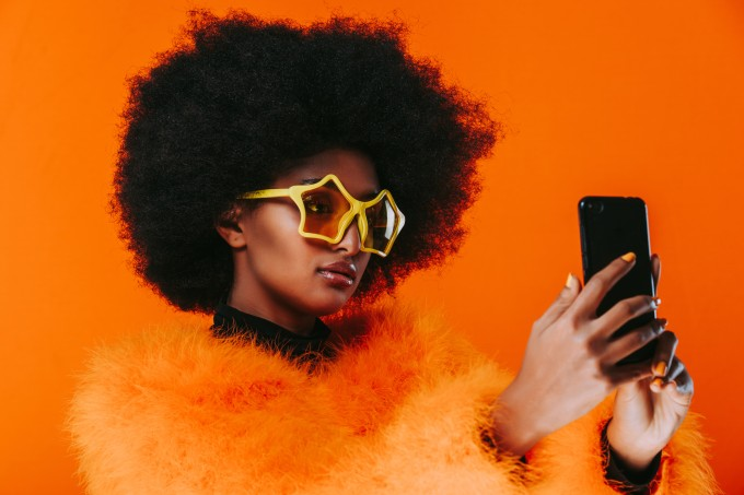 Young Woman Taking Selfie On Phone While Wearing Sunglasses Against Orange Background