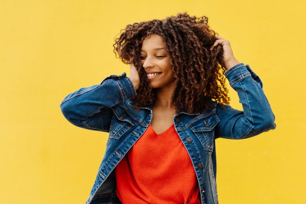 Mulher com cabelo cacheado mexendo no mesmo enquanto sorri